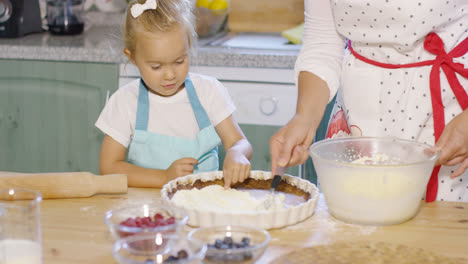 Pretty-little-girl-learning-to-bake-a-berry-pie