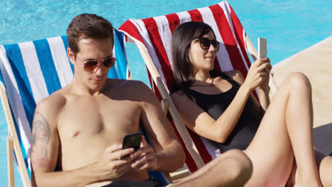 Young-couple-using-phones-at-the-swimming-pool