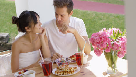 Couple-talking-at-breakfast-table-outside