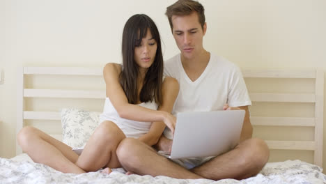 Woman-talking-to-man-using-laptop-while-in-bed