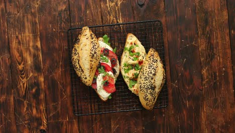 Fresh-organic-sandwiches-with-hummus-and-mozarella-cheese-placed-on-black-grill
