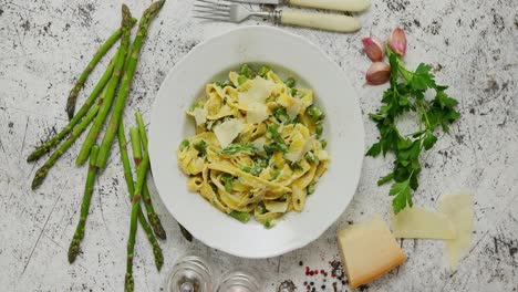 Homemade-tagliatelle-pasta-with-creamy-ricotta-cheese-sauce-and-asparagus-served-white-ceramic-plate