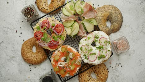 Delicious-Bagel-sandwiches-with-creamy-cheese-ham-hummus-salmon-and-vegetables