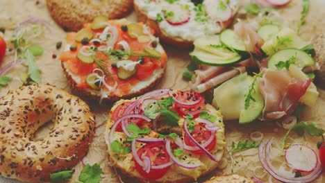 Bagel-sandwiches-with-various-toppings-salmon-cottage-cheese-hummus-ham-radish-and-fresh-herbs