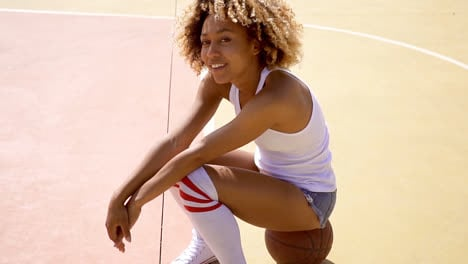 Attractive-female-athlete-sits-on-basketball