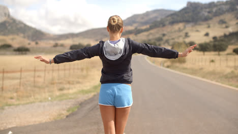 Back-Angle-of-Sporty-Girl-on-the-Road