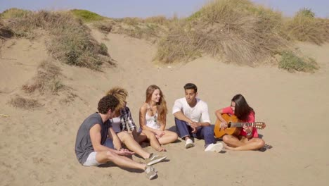 Group-of-young-multiracial-friends-playing-guitar