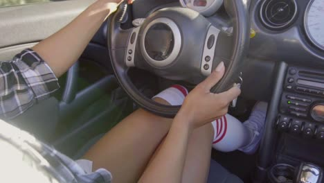 Close-up-on-woman-knees-while-driving-a-car
