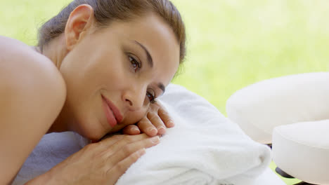 Woman-with-hair-up-in-a-bun-rests-on-folded-towel