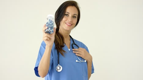 Young-brown-haired-doctor-in-scrubs-holds-bottle