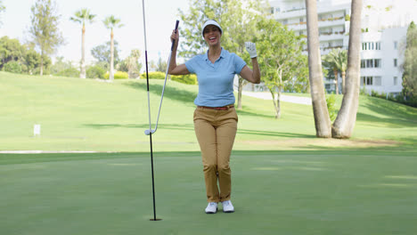 Woman-golfer-cheering-as-she-sinks-her-putt