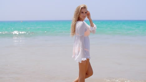 Pretty-Young-Woman-Standing-Against-Ocean