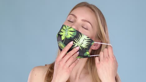 Beautiful-young-girl-taking-off-her-face-mask-against-viuses-with-huge-relief-