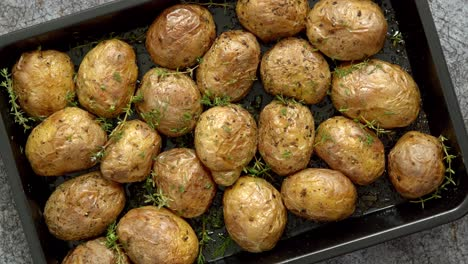 Oven-baked-whole-potatoes-with-seasoning-and-herbs-in-metalic-tray-Roasted-potatoes-in-jackets-