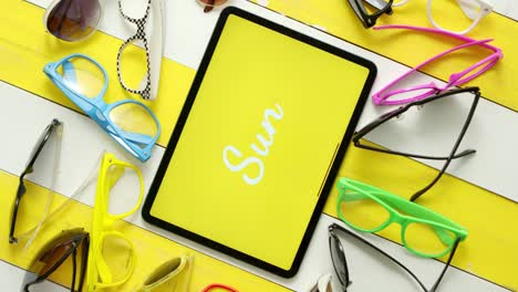 Various-style-shape-and-colour-sunglasses-Tablet-in-the-middle-with-text-SUN-