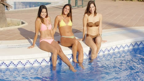 Three-happy-women-sitting-on-the-side-of-a-pool