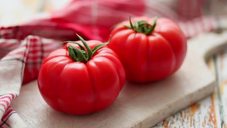 Two-fresh-eco-tomatoes-placed-on-white-wooden-cutting-board-Healthy-food-concept