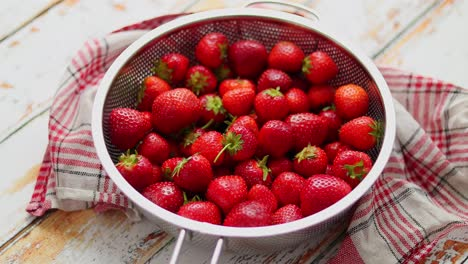 Freshly-harvested-strawberries-Metal-colander-filled-with-juicy-fresh-ripe-strawberries-on-an-table