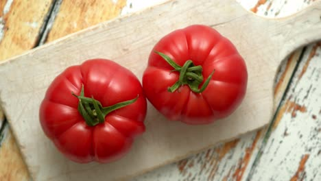 Top-view-of-a-white-cutting-board-with-a-fresh-juicy-tomatoes-on-a-wooden-table
