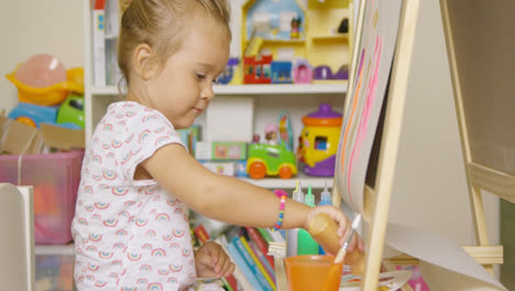 Little-girl-having-fun-painting-with-water-colors