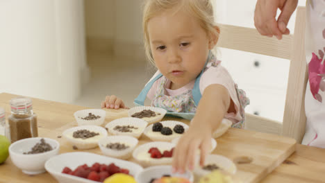 Little-girl-reaching-for-berries-on-muffins