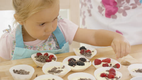 Cute-little-girl-putting-berries-on-muffins