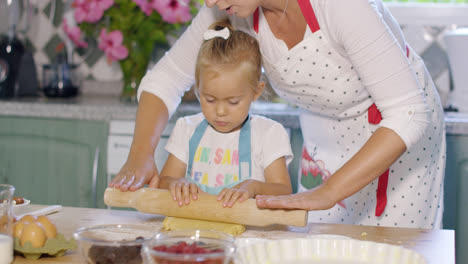 Mother-rolling-out-pastry-with-a-little-helper