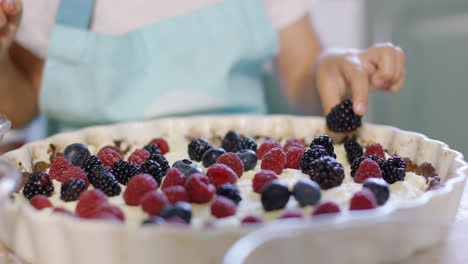 Little-girl-placing-a-blackberry-on-a-pie