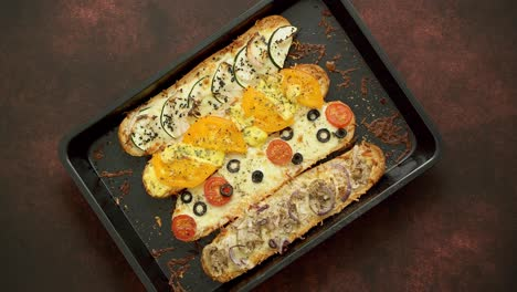 Long-baguettes-pizza-sandwiches-with-tuna-mushrooms-tomatoes-and-cheese-on-a-metal-baking-tray