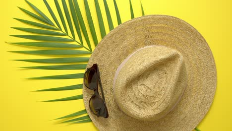 Straw-hat-green-palm-leaf-and-sunglasses-on-yellow-backdrop-Summer-concept-Flat-lay-top-view