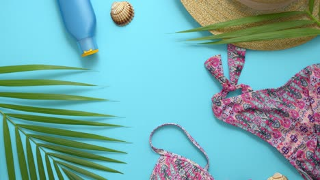 Women-beach-summer-clothes-and-accessories-collage-on-blue-background