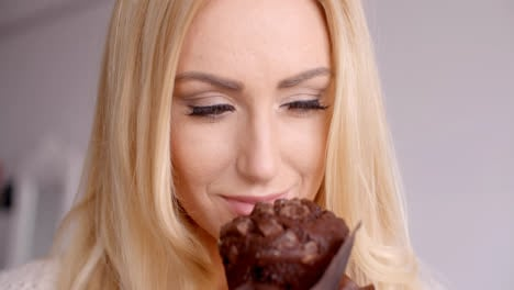 Blond-Woman-Looking-at-Chocolate-Cupcake-Closely