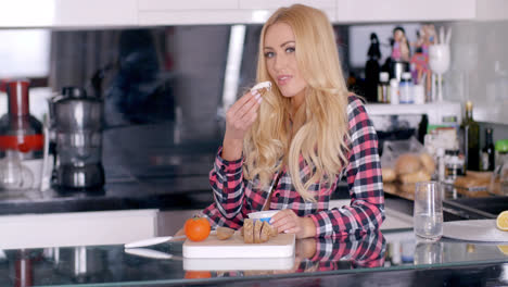 Pretty-Blond-Woman-Eating-a-Bread-at-the-Kitchen