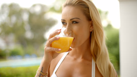 Woman-Drinking-Glass-of-Orange-Juice-Outdoors