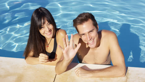Smiling-couple-standing-in-clear-pool-wave