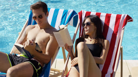 Young-couple-reading-books-at-the-swimming-pool