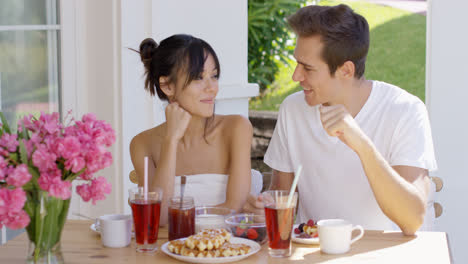 Attractive-couple-enjoying-breakfast-outdoors