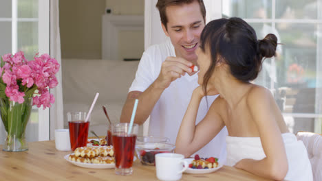Man-feeding-his-wife-fruit-at-breakfast