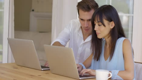 Man-and-woman-working-on-laptop-computers-together
