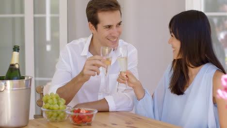 Cheerful-couple-toasting-champagne