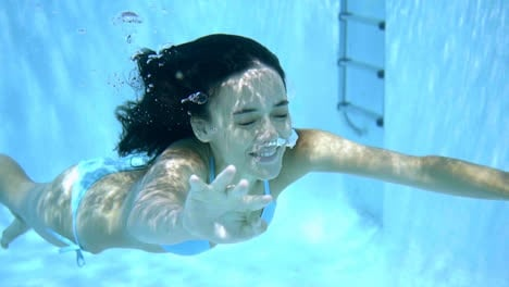 Young-woman-swimming-underwater-with-closed-eyes