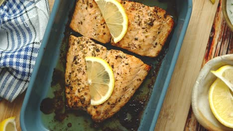 Close-up-shot-of-healthy-grilled-salmon-served-in-heat-proof-ceramic-dish-Placed-on-wooden-board