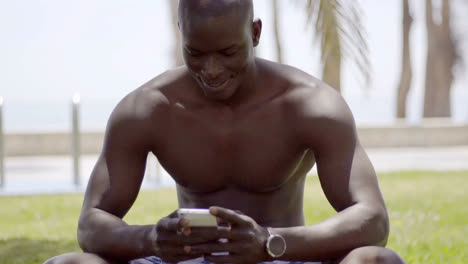 Close-up-of-smiling-black-man-checking-his-phone