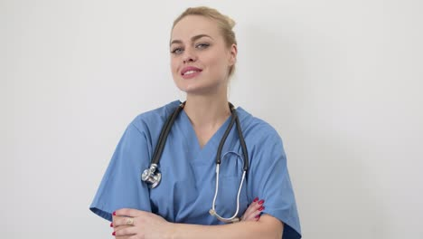 Female-doctor-in-blue-medical-coat-standing-isolated-with-arms-crossed-Looking-at-camera