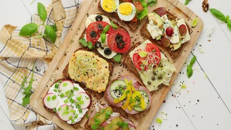 Tasty-homemade-small-sandwiches-with-various-ingredients-served-on-wooden-chopping-board