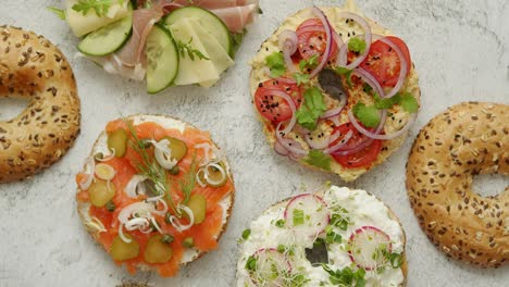 Homemade-Bagel-sandwiches-with-different-toppings-salmon-cottage-cheese-hummus-ham-radish