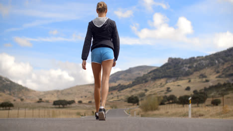 Fitress-Girl-Walking-on-the-Road-in-Mountains