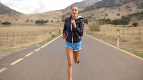 Fitress-Girl-Running-on-the-Road-in-Mountains