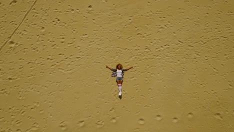 View-from-above-of-woman-laying-in-sand
