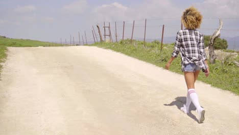 Young-woman-running-along-a-rural-dirt-road